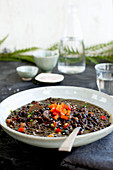 Black Lentil Sesame Coconut Soup served with sparkling water