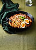 Japanese ramen with pork belly, mushrooms and marinated eggs on green linen tablecloth