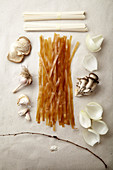 Asian cuisine ingredients on paper background: Red rice noodles, udon noodles, onion, garlic and oyster mushrooms