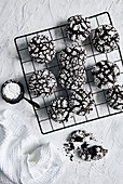 Chocolate crinkle cookies on wire cooling rack with icing sugar dusting
