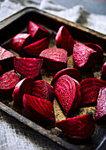 Raw cut beetroot on a dark rustic baking tray