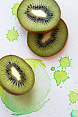 Kiwi slices on a paper background with green splashes of colour
