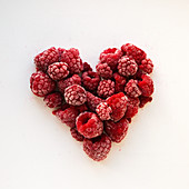 A heart of frozen raspberries on a white background
