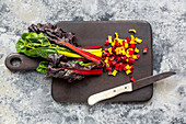 Brightly coloured swiss chard sliced on a wooden board with a knife