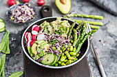 A veggie bowl with bulgur wheat, asparagus, avocado, radishes, cucumber, mangetout, edamame and red sprouts