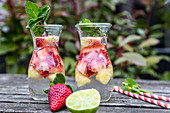 Jugs of detox water with strawberries, lime and mint on a garden table