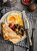 Cooked vegetarian breakfast consisting of eggs mushrooms toast and ketchup with coffee pot