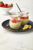 Sweet avocado cream with strawberry sauce, layered in glasses