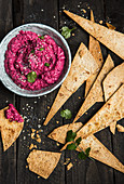 Beetroot hummus with tortilla chips for dipping (top view)