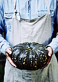Whole pumpkin in farmers hands