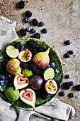Frischer Obstteller mit Feigen, Limetten, Blaubeeren, Brombeeren und Maracuja