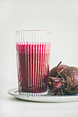 Fresh morning beetroot smoothie or juice in glass, white background
