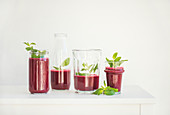 Fresh morning beetroot smoothie or juice in glasses with mint, white background, copy space