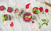 Fresh morning beetroot smoothie or juice in glasses with mint leaves over grey marble background, top view