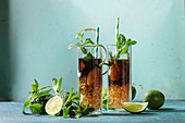Two Glasses of classic Cuba libre cocktail with lime, mint, crushed ice and cola, served with ingredients above and retro cocktail tubes