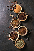 Variety of grounded, instant coffee, different coffee beans, brown sugar, spices in wooden bowls over dark texture background