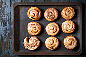Homemade glazed puff pastry cinnamon rolls with custard and raisins on oven tray over old dark blue wooden background