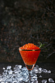 Glass of red caviar decorated by fresh rosemary on crushed ice over dark background