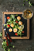 Fried scallops with lemon, cherry tomatoes and green salad served on wooden black slate serving board with cutlery and glass of white wine over old dark metal background