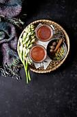 Heisser Kakao mit Gewürzen und Blütenzweigen auf Korbtablett (Aufsicht)