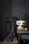 Winterlicher Kokos-Käsekuchen auf Tortenständer und rustikalem Holztisch