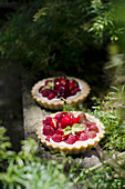 Cherry and raspberry tarts on a wooden rustic table
