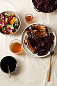 Grilled pork ribs in thick barbeque sauce garnished with red cabbage and beets braised in red wine sauce