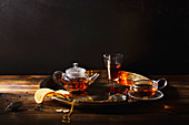 Small glass teapot and glasses with hot black tea, dried rose petals, pocket magnifier on golden chain, squeezed orange slice on golden tray