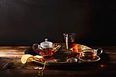 Teatime: Glasteekanne, Teeglas und Teetasse auf goldenem Tablett
