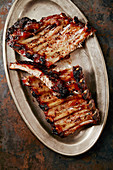 Flavorful grilled pork ribs in thick barbeque sauce cut in messy way served in vintage metal tray