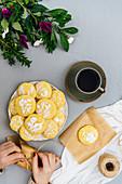 Frau wickelt Zitronenplätzchen in Papier (Aufsicht)