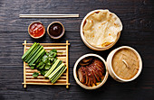 Sliced Peking Duck in bamboo steamer served with fresh cucumber, green onions, cilantro and roasted wheaten chinese pancakes with sauce Hoysin
