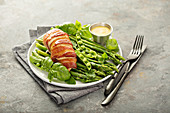 Bacon wrapped chicken breast with asparagus and spring peas