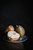 Birnen, ganz und halbiert, auf Teller