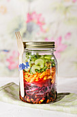 Low-carb oriental rainbow layered salad in a jar to take away