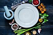 Verschiedene Gewürze und Gemüsesorten um leeren Teller