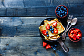 Crepes with fresh berries on rustic wooden background