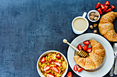 Delicious breakfast table with corn flakes, fresh croissants, honey, ripe strawberry and coffee