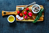 Wooden cutting board with tasty organic vegetables, olive oil and spices on dark vintage background