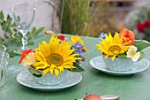 Kleine Gestecke mit Sonnenblumen und essbaren Blüten