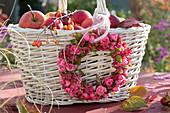 Pinker Herbst-Kranz aus Rosen und Pfaffenhütchen an Korb