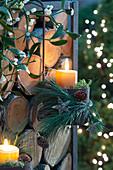 Kerzen weihnachtlich im Hängetopf am Brennholz-Regal