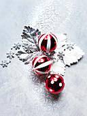Red and white Christmas baubles on silver leaves