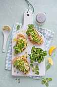 Grilled ciabbata toped with cream cheese peas spread, peas, salad and lemon with lemon zest, view from above