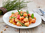 Gnocchi with tomato sauce, rocket and pine nuts