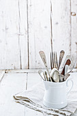 Vintage cutlery in a white porcelain jug