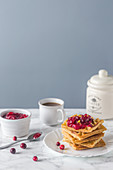 Waffles served with cranberry sauce and coffee