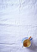 Öl im Porzellankännchen mit Kochlöffel
