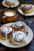 Yeast buns cinnamon on a plate and a mug of milk