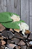 Wollkügelchen in Kissenbezügen auf Holzstapel